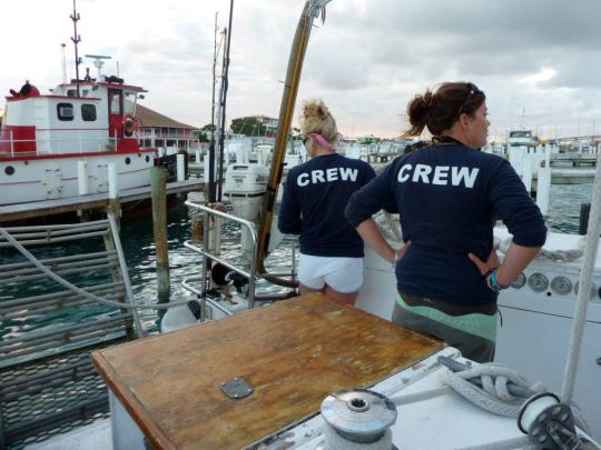 Some of the crew members getting ready to help dock the boat.